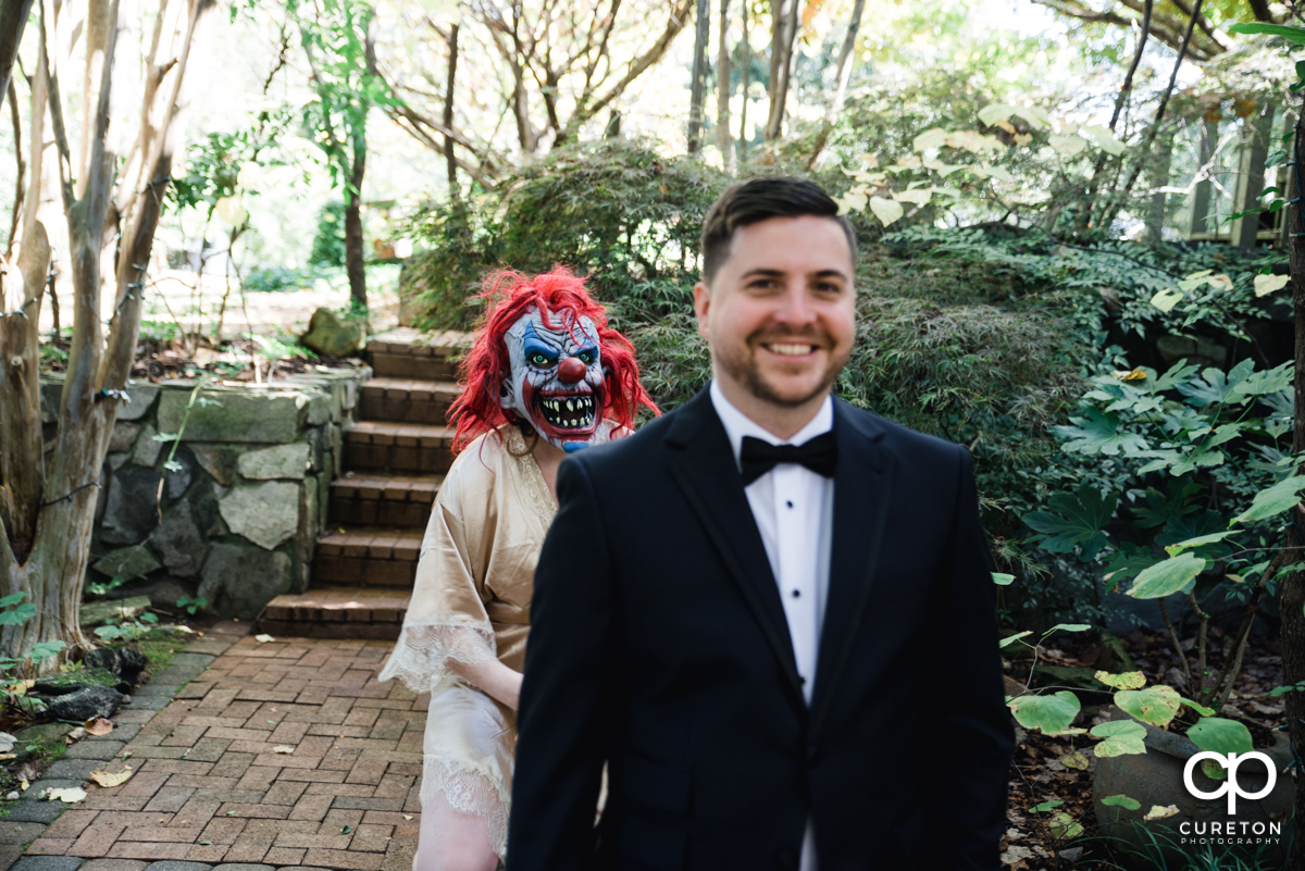 Bride wearing a clown mask walking up behind her groom at a first look.