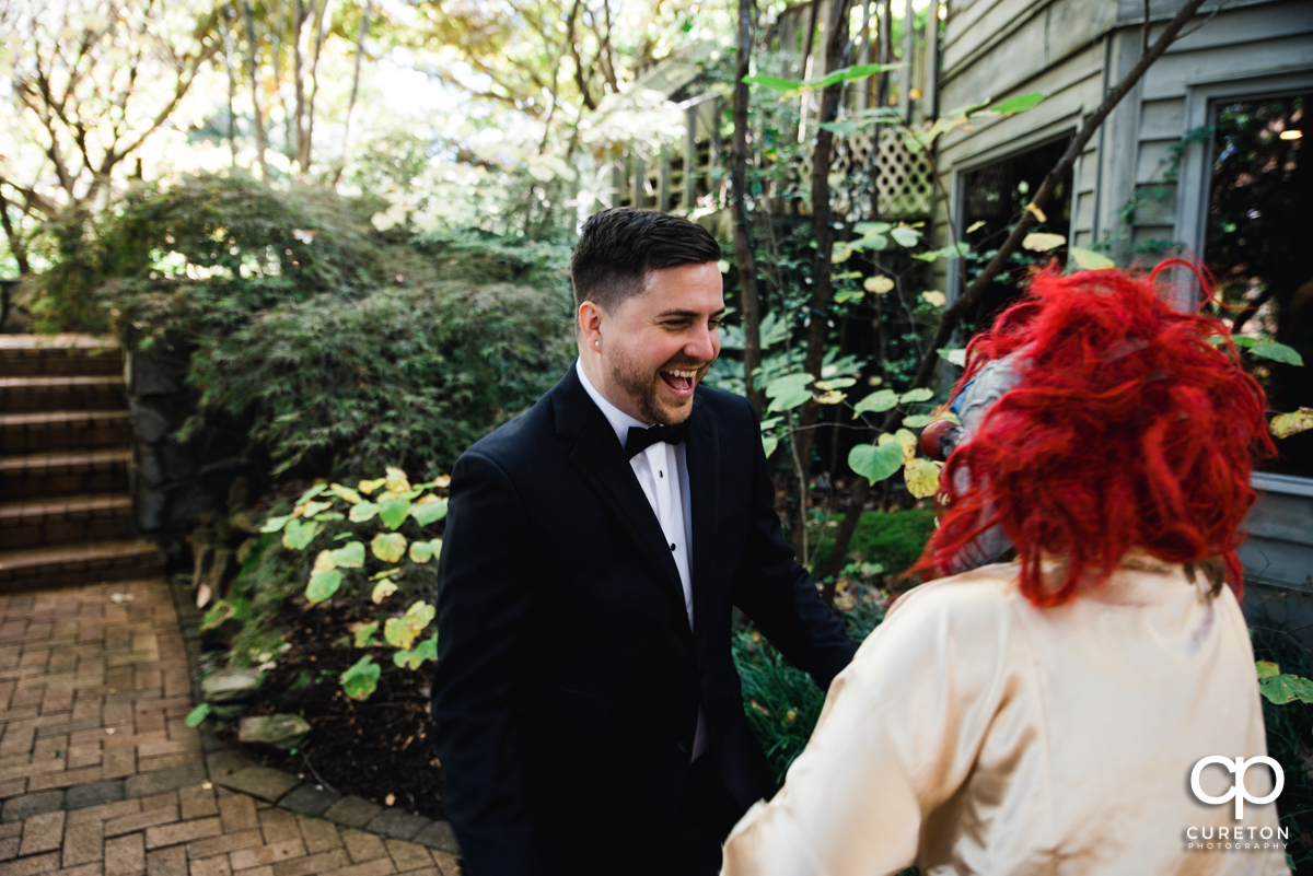Groom laughing as he sees his bride wearing a clown mask.
