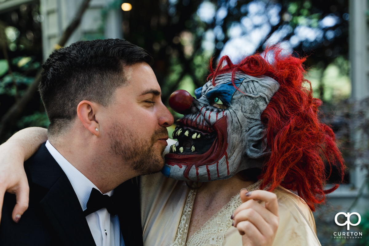 Groom kissing his bride in a clown mask on their wedding day.