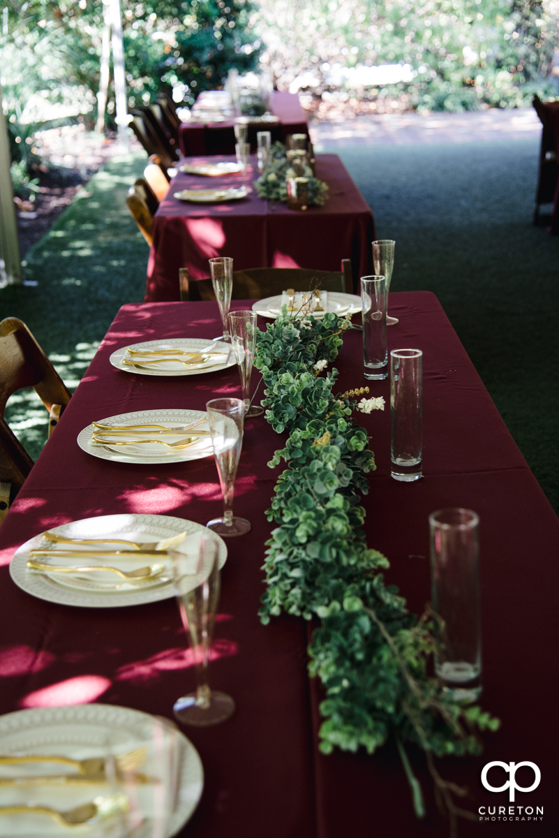 Long table at the wedding reception decorated with florals.