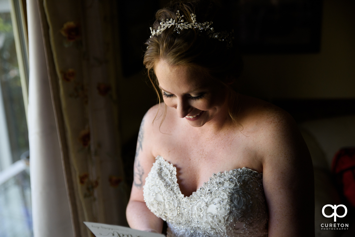 Bride reading a note from her groom before the ceremony.