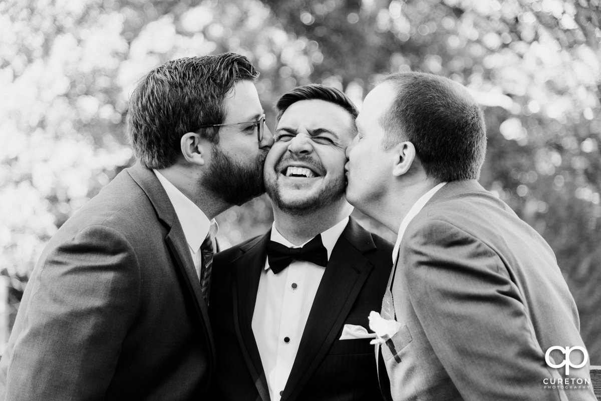 Groom's brothers kissing him on the cheek.