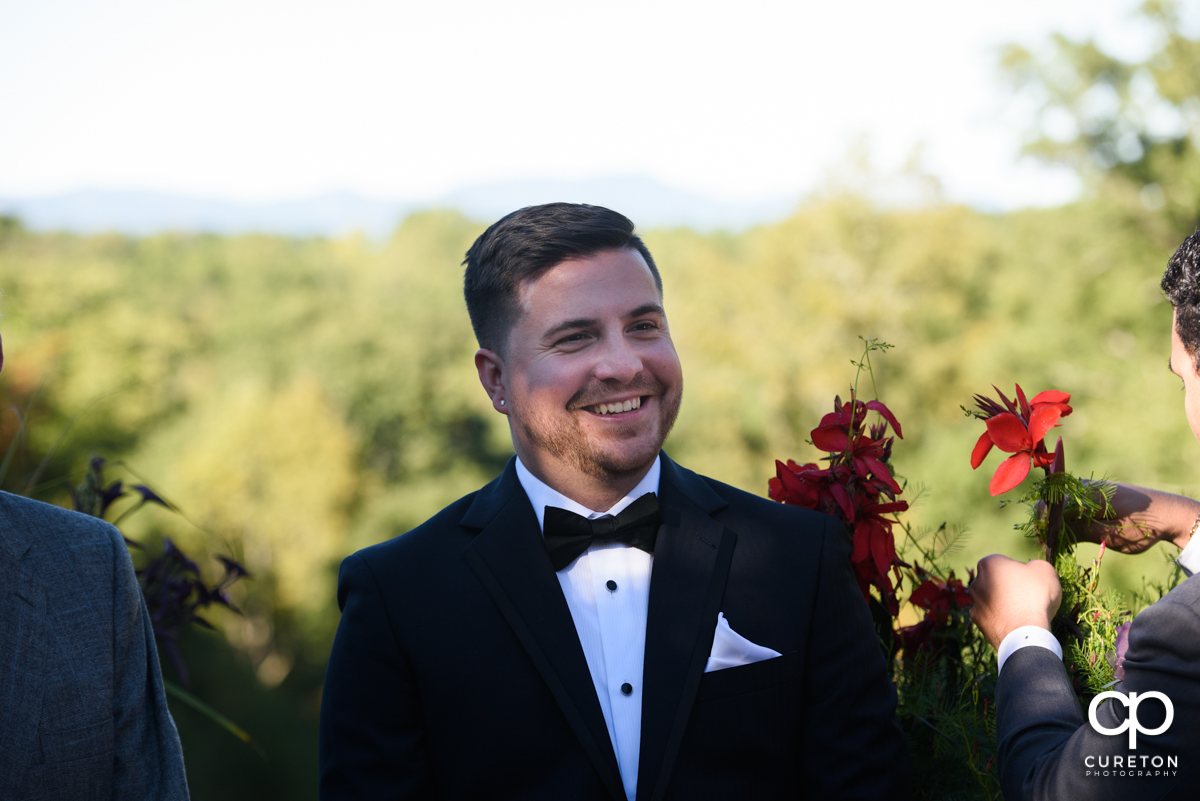 Groom smiling as he sees his bride walking down the aisle.
