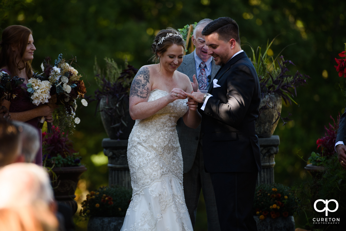 Bride putting a ring on the grooms finger.