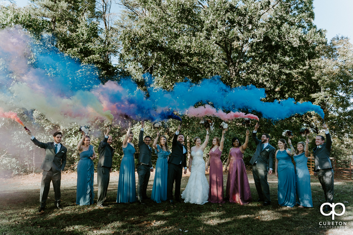Wedding party holding smoke bombs after the wedding ceremony in Greenville,SC.