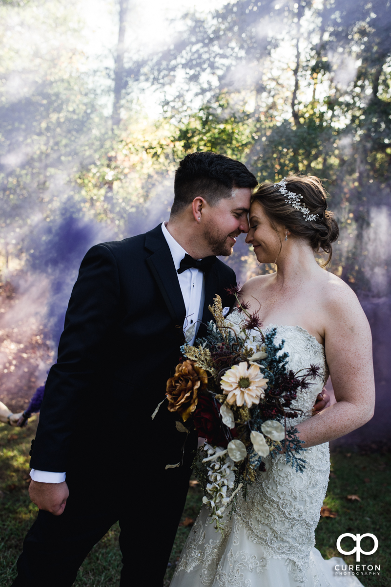 Bride and groom nose to nose in a cloud of purple smoke.