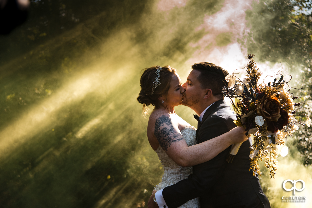 Bride kissing her groom in a cloud from a yellow smoke bomb at the wedding.