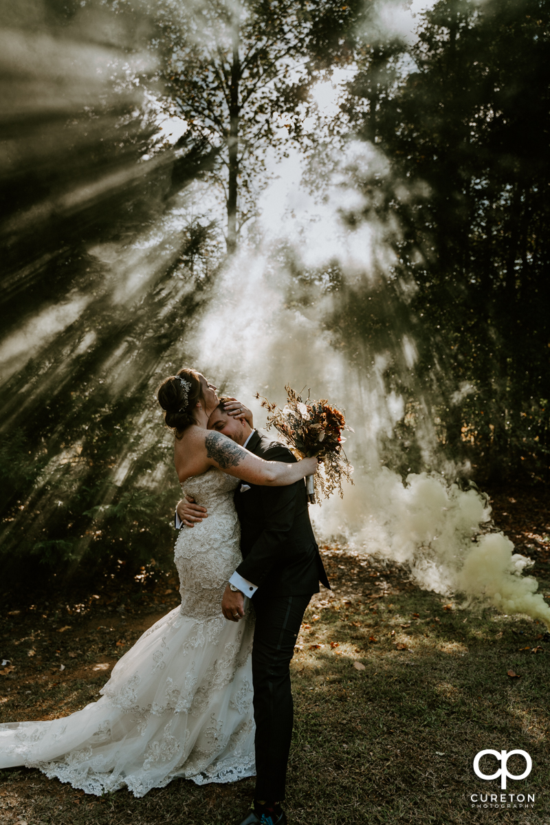 Bride holding her groom as smoke from a smoke bomb fades into the sunlight at the wedding.