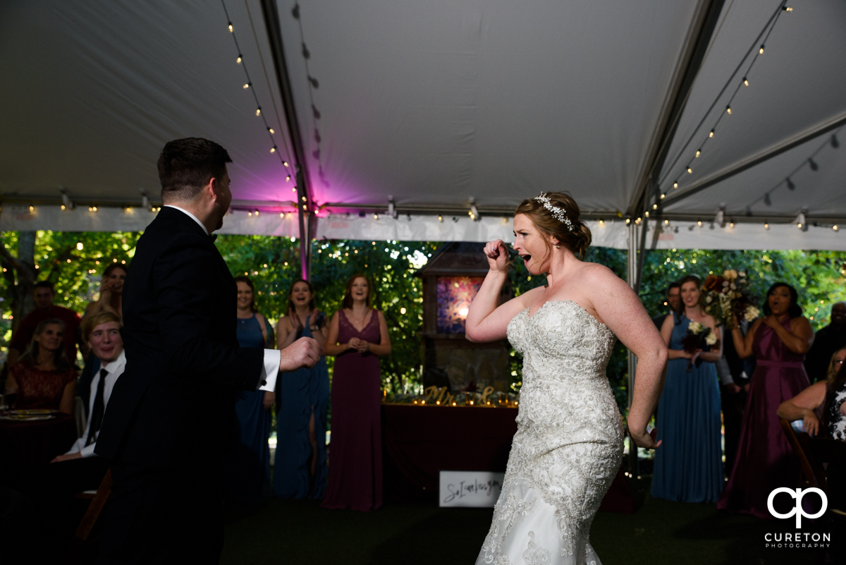 Bride and groom having a dance off as they inter their wedding reception.