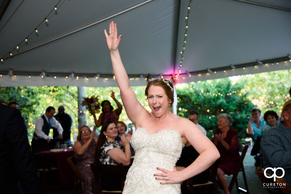 Bride cheering as she has a dance off with her husband at the reception.