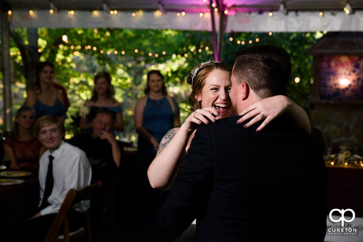 Bride smiling while dancing with her husband.