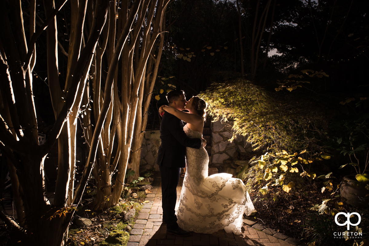 Bride and groom kissing as they slow dance in the garden at their wedding at The Viewpoint at Buckhorn Creek.