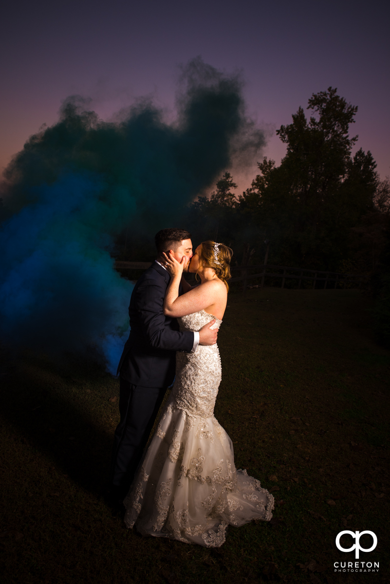 Bride and groom kissing at sunset in front of a blue smoke bomb on their wedding day.