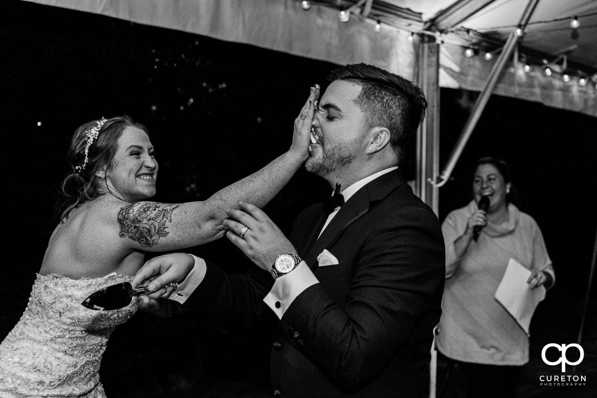 Bride smashing cake into her grooms face.