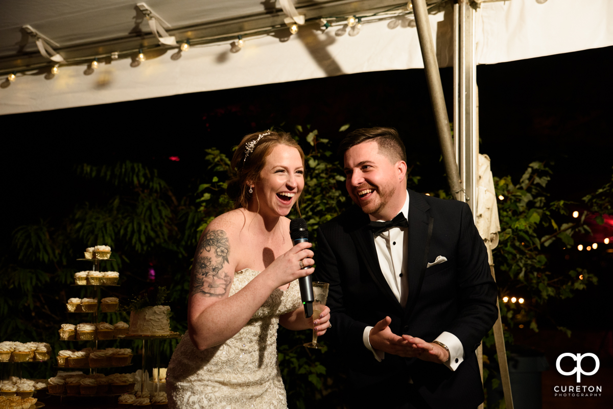 Bride and groom laughing as they give a welcome speech at their wedding reception.