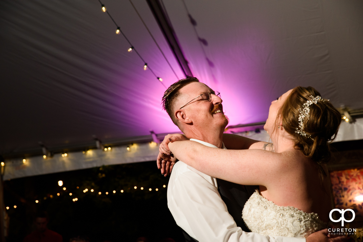 Bride having a laugh with her father as they dance at her wedding reception.