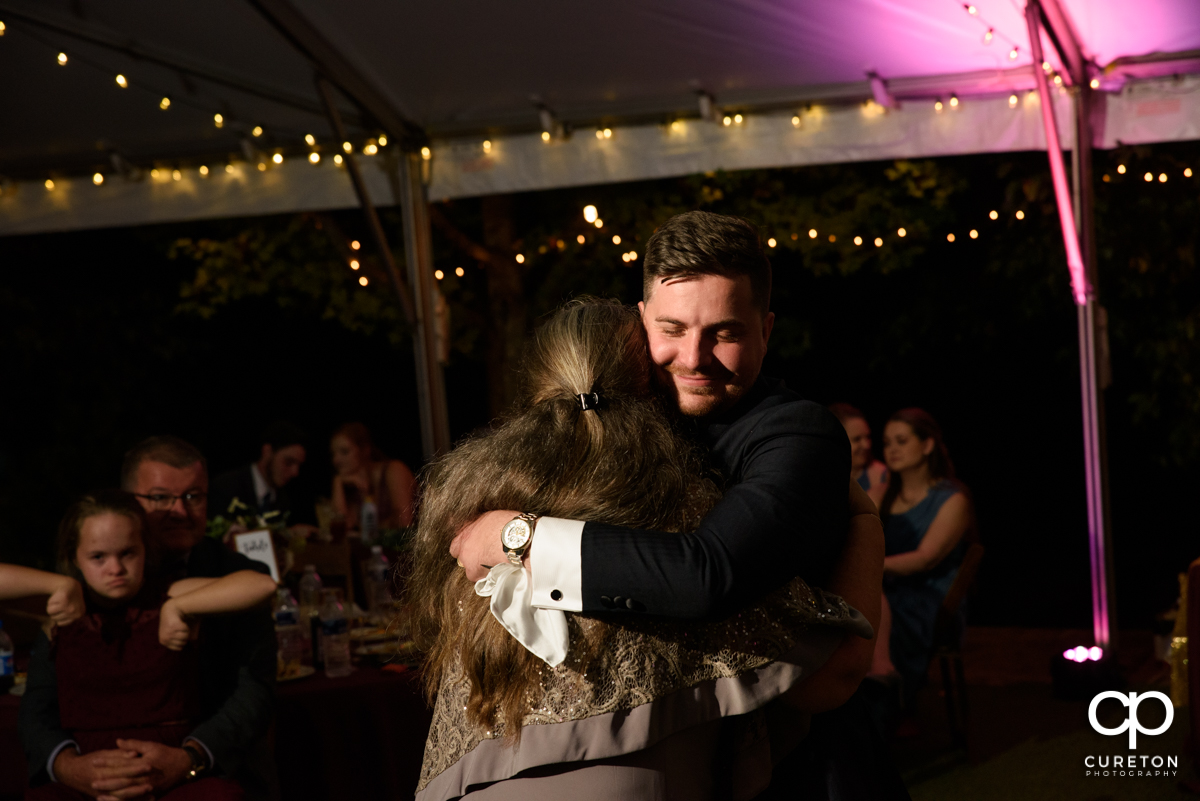 Groom hugging his mom as they dance at the wedding reception.