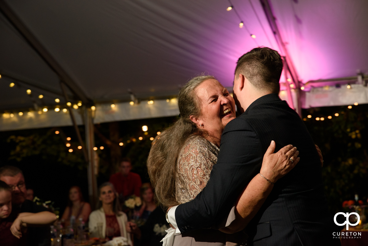 Groom and his mom laughing as they share a dance at the wedding reception.