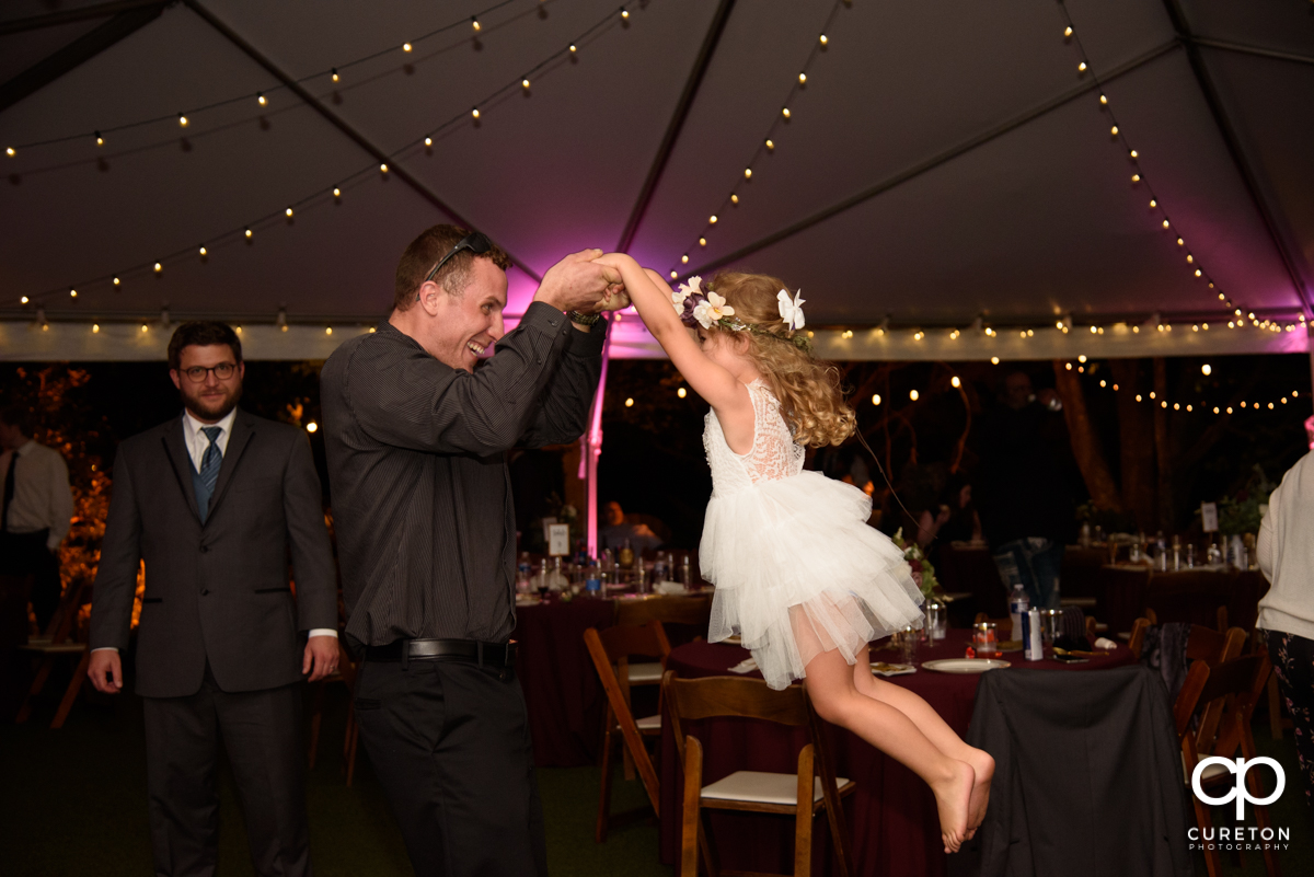 Wedding guest dancing with his young daughter.