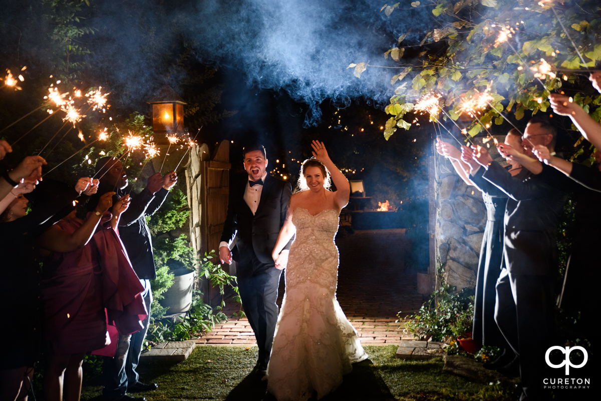 Bride and groom leaving The Viewpoint at Buckhorn Creek though sparklers.