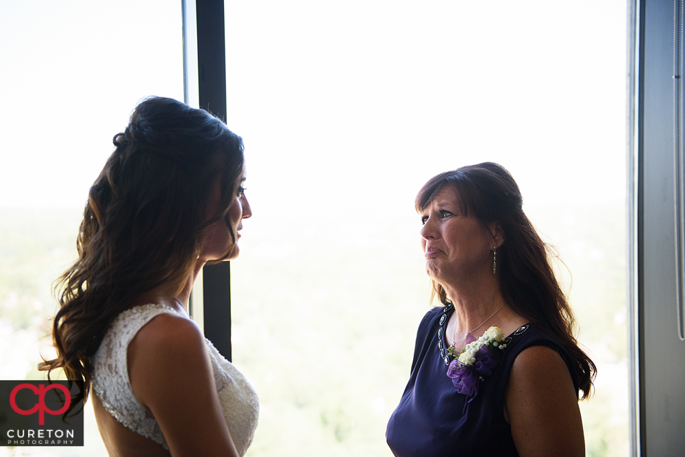 Mother of the bride crying when she sees her in the dress.
