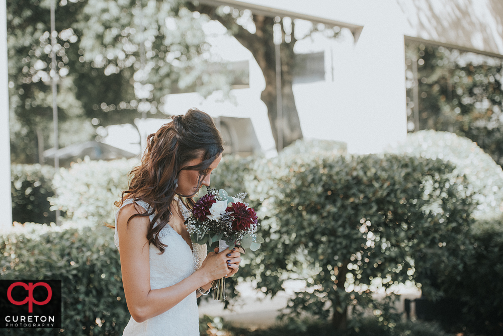 Bride smelling her flowers.