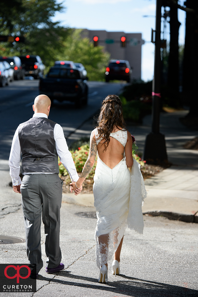 Bride and groom walking down the street downtown.