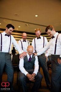 Groomsmen praying over the groom.