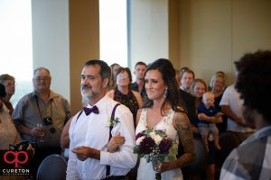 Bride and her father walking down the aisle during the ceremony.
