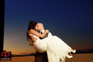 Groom carrying the bride at sunset.