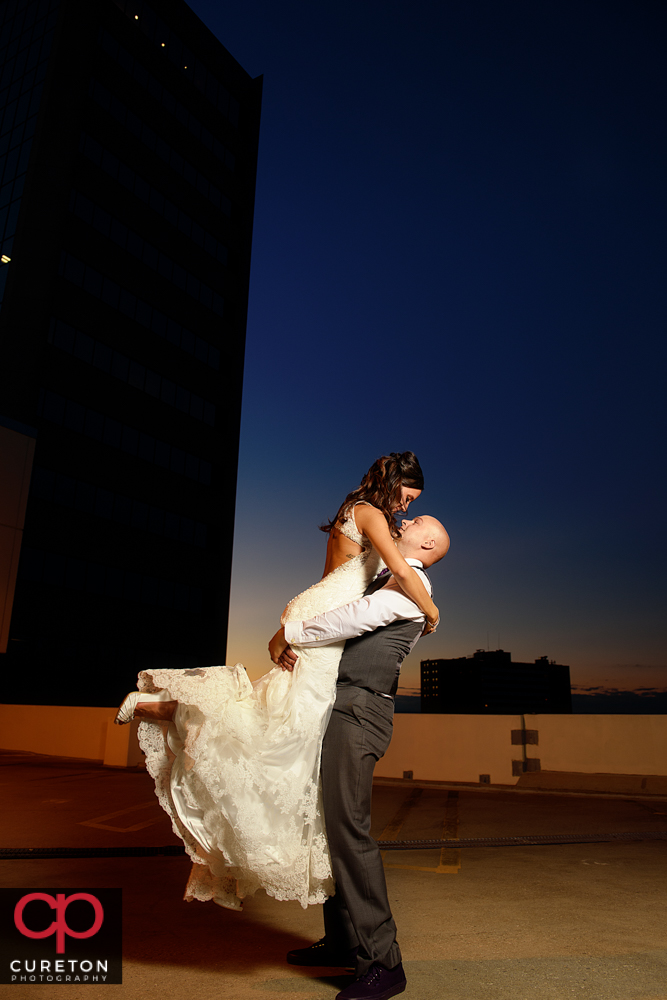 Groom lifting the bride at sunset during the commerce club wedding reception.