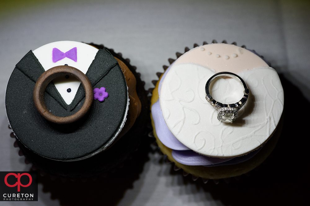 Wedding rings on top of cupcakes.