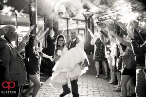 Groom carrying the bride through sparklers at the end of the wedding.