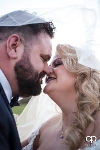Bride kissing her groom under a veil.