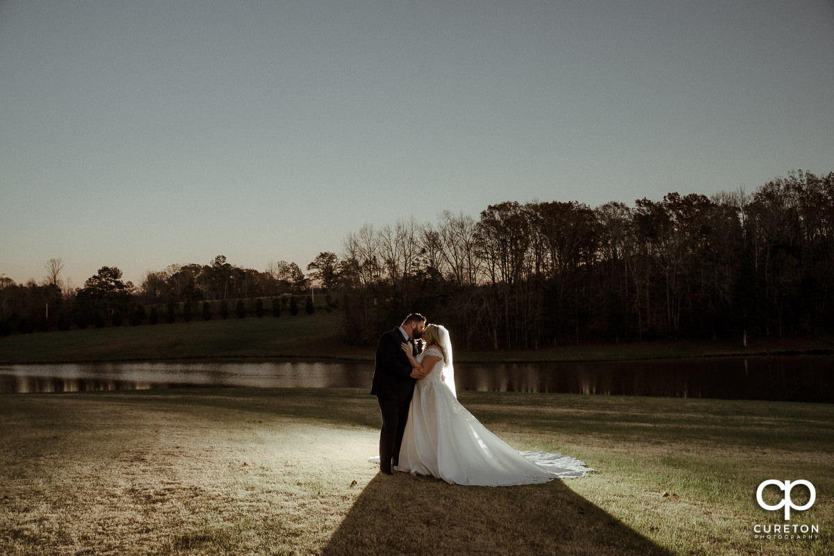 Bride and groom kissing in front of a pond at sunset.