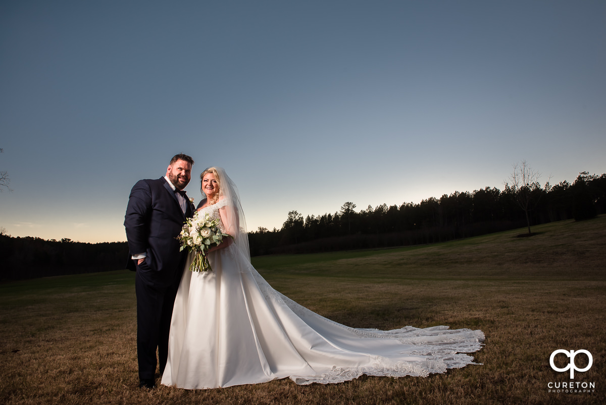 Bride and groom in a pasture.