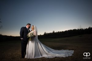 Bride and groom at sunset in a field.