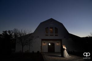 Groom and bride hugging in front of a white barn.