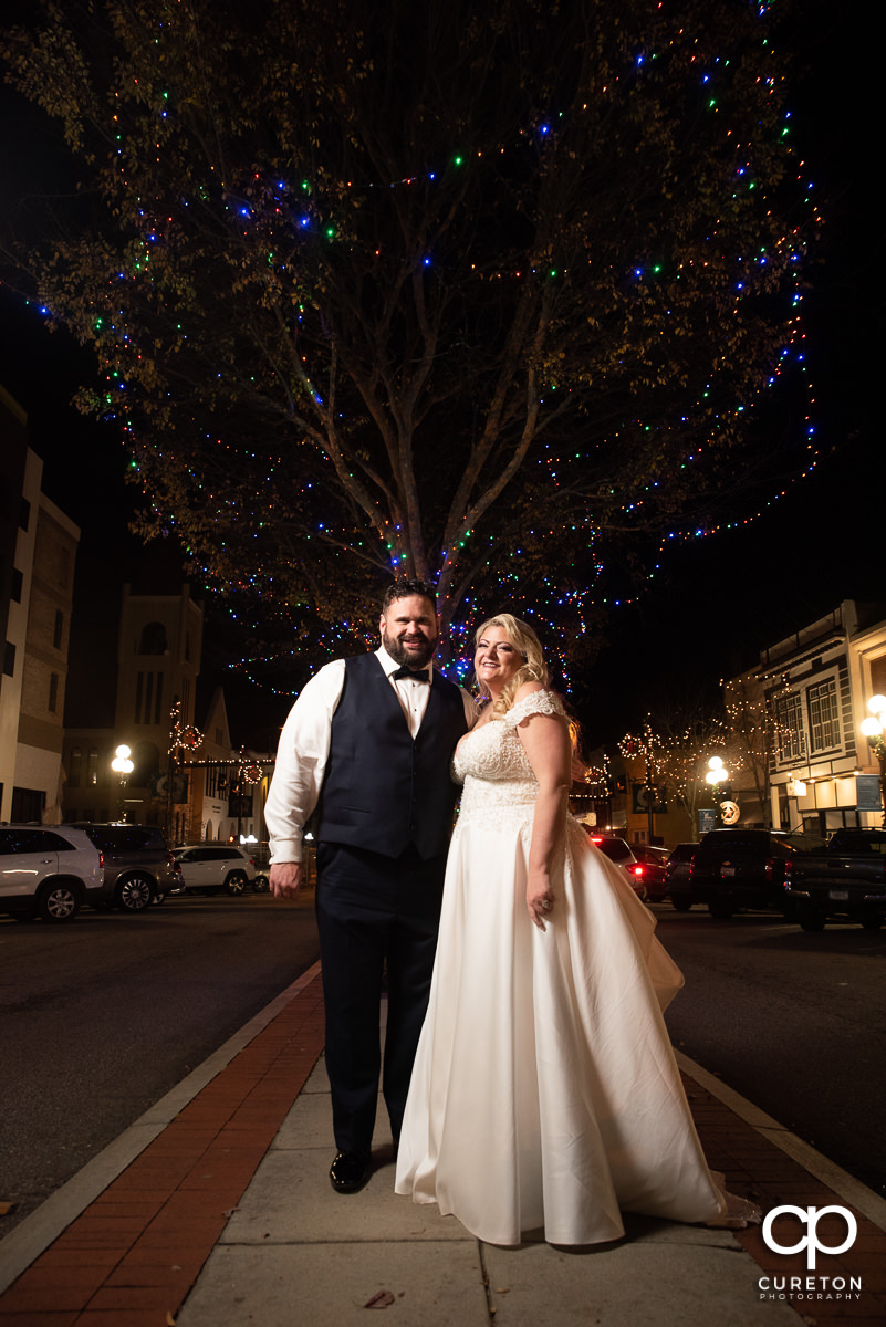 Bride and groom under Christmas lights in downtown Anderson,SC.
