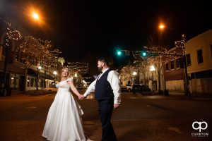 Bride and groom walking in a crosswalk in downtown Anderson.