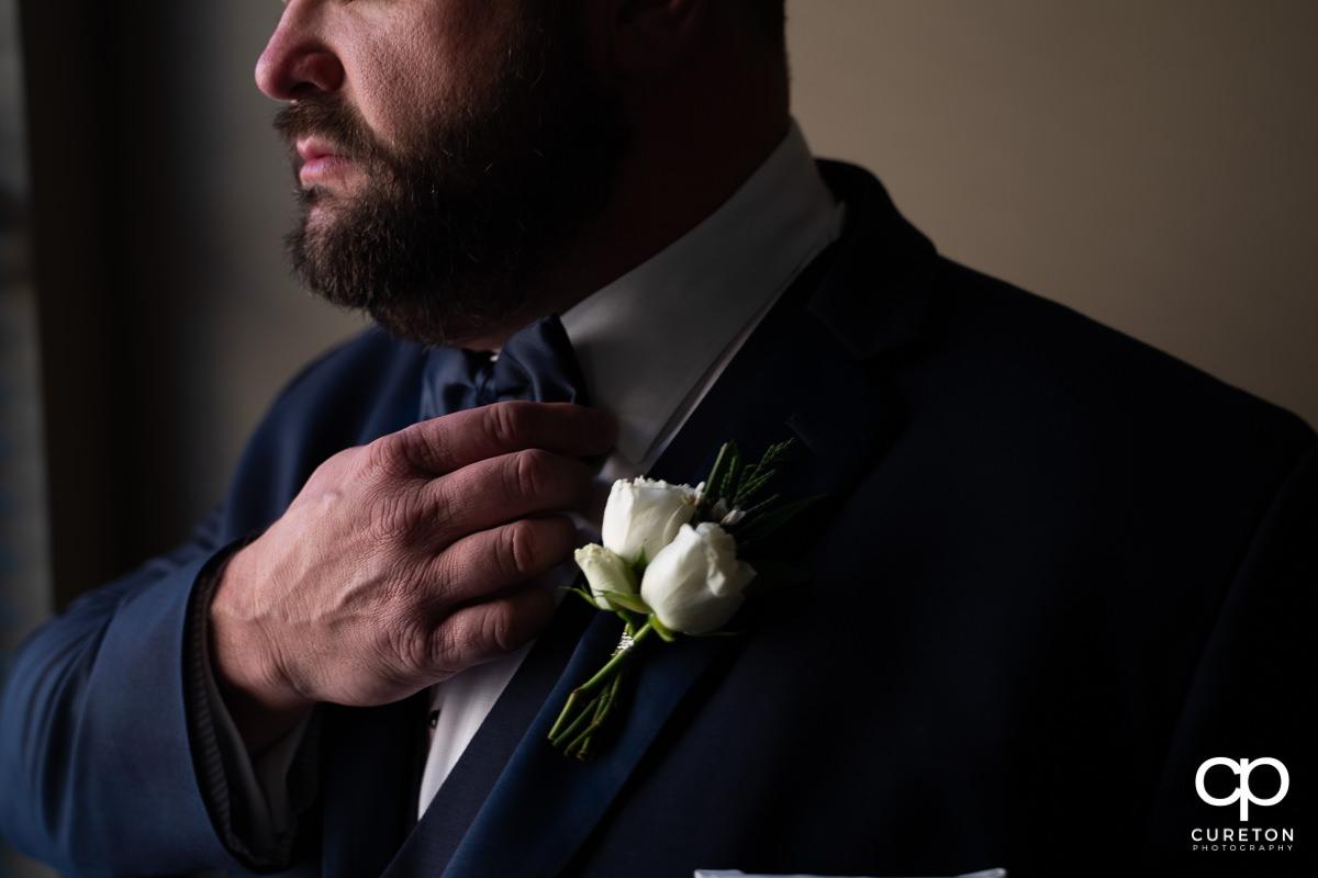 Groom adjusting his tie.