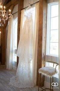 Bridal dress hanging in a window.