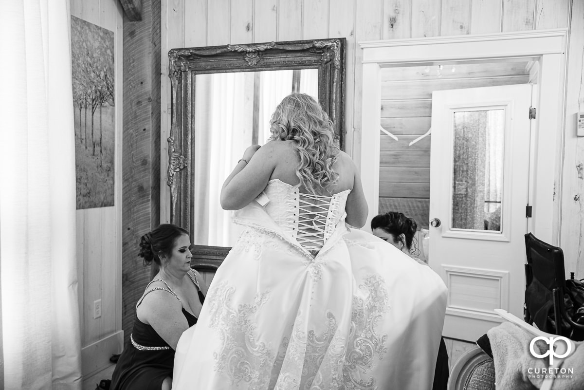 Bride putting a dress on.