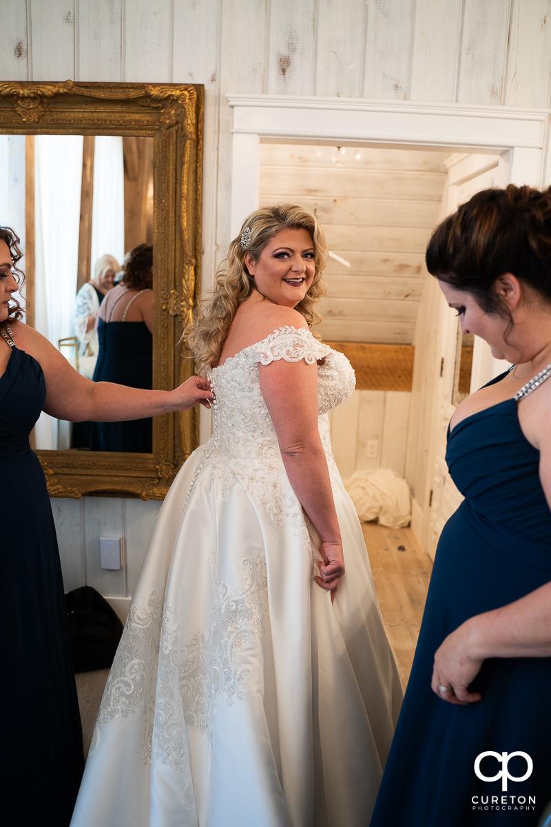 Bridesmaids helping the bride get dressed.