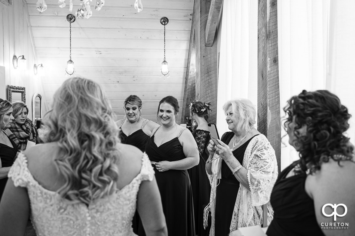 Bridesmaids seeing the bride in her dress.