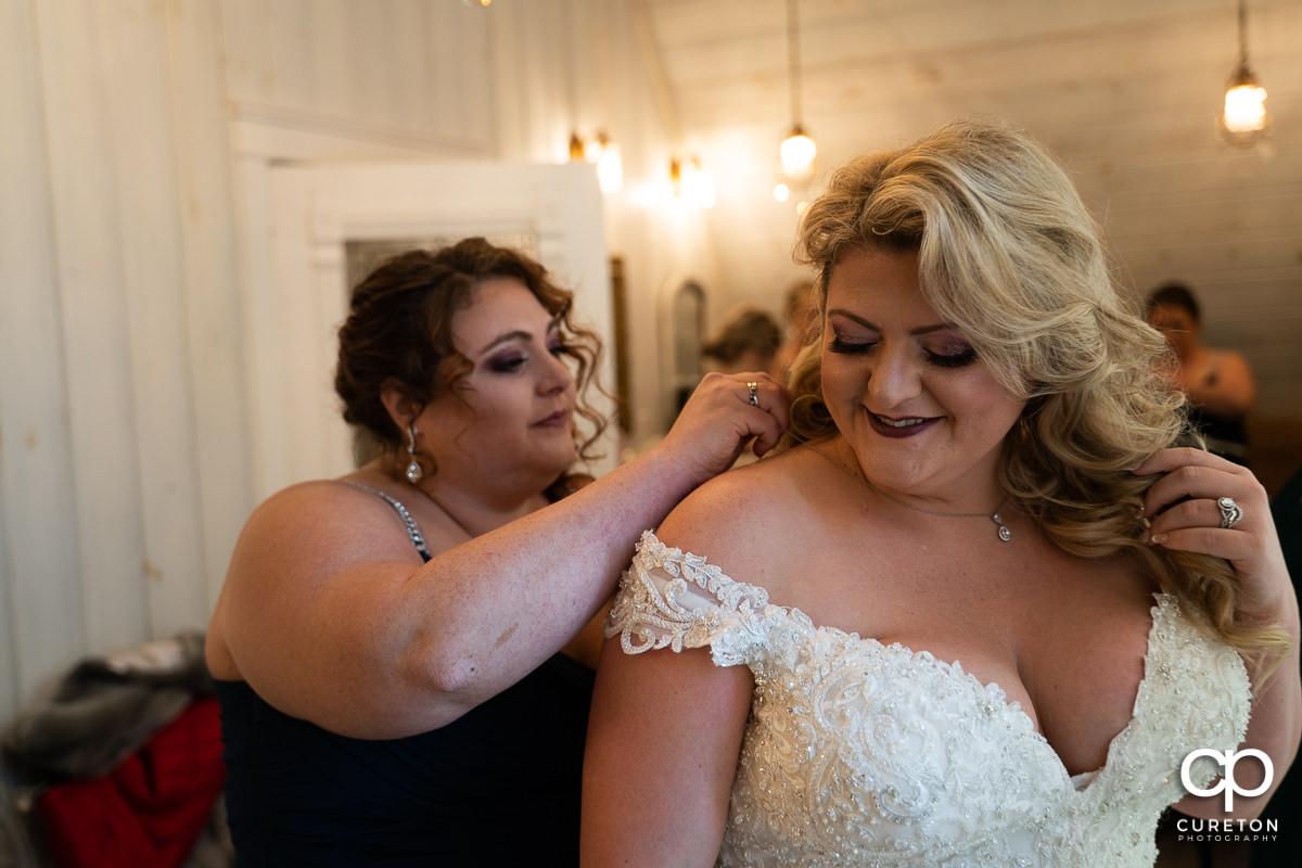Bride putting on jewelry.