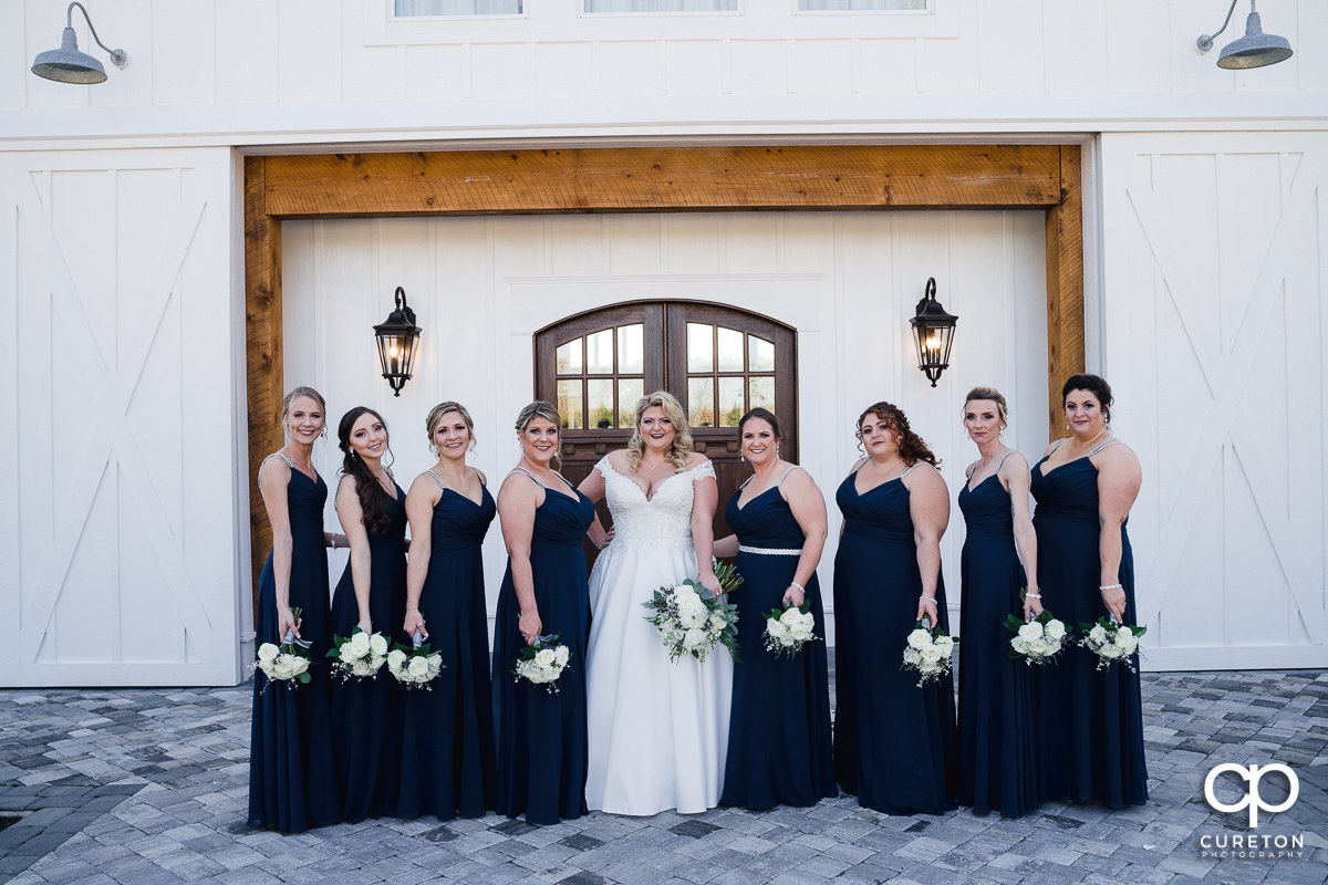 Bride and bridesmaids posing in front of a white barn.