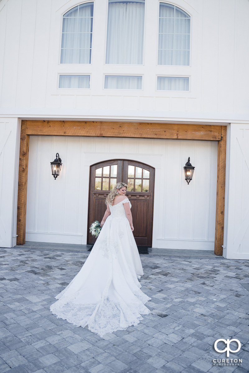 Bride walking into a white barn.