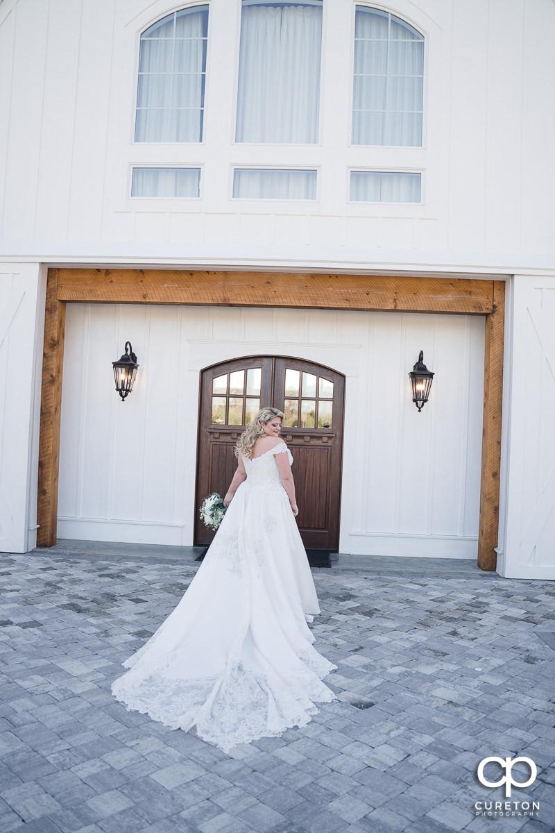 Bride walking into a white barn.