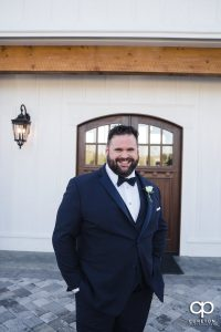Groom in front of a white barn.